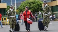 A woman is helped by Colombian soldiers crossing the Simon Bolivar international bridge from Venezuela