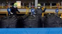 workers at a plant handling radioactive soil