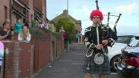 Person playing bagpipes in the street