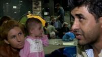 Ismail, who is from northern Syria, sits in Budapest train station with his family