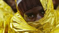 A migrant waits to disembark from a Coast Guard ship in the Sicilian harbour of Messina