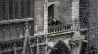 Workmen on a balcony in Notre Dame, which is covered in scaffolding
