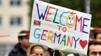 "People welcome refugees with a banner reading ""welcome to Germany"" in Dortmund, Germany, Sunday, Sept. 6, 2015"