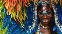 A performer poses for a photograph on the second day of the Notting Hill Carnival