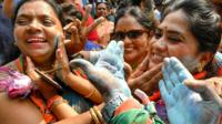 "Indian supporters and party workers of Bharatiya Janata Party (BJP) put colour powder on their faces as they celebrate on the vote results day for India""s general election in Bangalore on May 23, 2019."