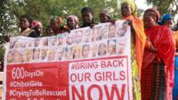 "Members of the ""Bring Back Our Girls"" movement, holding a banner showing photographs of some of the missing"