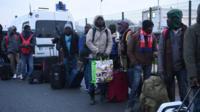 "Migrants queue at the ""Jungle"" camp in Calais, France."