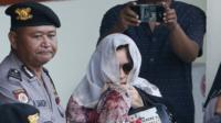 Schapelle Corby in sunglasses with a scarf over her head and part of her face, surrounded by police