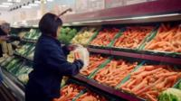 Women picking carrots at a supermarket