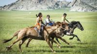 Mongolian children riding horses