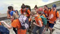 Team pushing wheelchair user up Snowdon