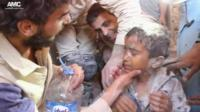 Young boy being given water after being rescued from rubble
