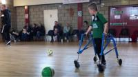 A boy uses a frame to play football