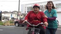 A woman rides a bike helped by a volunteer