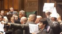 MPs protest around the Speaker's chair