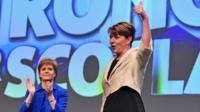 Leanne Wood gives a thumbs up on stage, applauded by Nicola Sturgeon