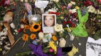 Flowers, candles and chalk-written messages surround a photograph of Heather Heyer on the spot where she was killed