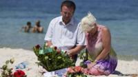 Tourists mourn at the site of a shooting attack on the beach