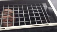 Задержанная на акции в Москве в окне автозака.