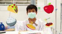Thai boy wearing a hospital mask with food emojis around him