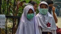 Indonesian schoolgirls wear facemasks
