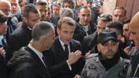 Emmanuel Macron in a crowd, talking to Israeli security