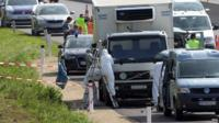 Forensic experts investigate a truck in which migrants were found dead as it stands on freeway autobahn A4 between Parndorf and Neusiedl, Austria
