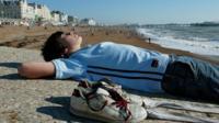 Boy sunbathing on beach