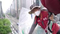Kim Yong-Hee looks at the camera from the top of the 20m high traffic tower