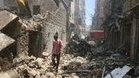 A man walks through the rubble of Aleppo, Syria