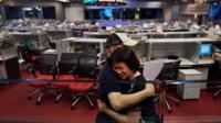 Two stock brokers hug on Hong Kong's trading floor