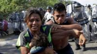 Migrants, mainly from Central America, react as members of the security forces approach to them