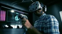 A man using a virtual reality headset and controls