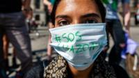 A protester wears mask with #SOSAmazonia on it