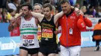 Matthew Rees of Swansea Harriers helping an ailing David Wyeth of Chorlton Runners