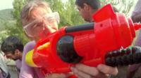 Reporter Rafael Estefania holding a water pistol