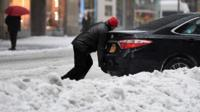 Man pushes car in snow in New York