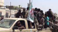 Houthi fighters clamber on the back of a pickup truck