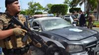 Lebanese security forces stand next to a vehicle damaged in a gun attack in Tripoli (4 June 2019)