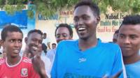 Abdunasir Mohamed in blue football shirt with supporters