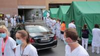 Hospital staff turn their backs