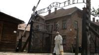 Pope Francis walks through the Auschwitz camp gates