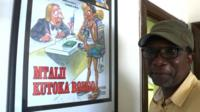 Tanzanian cartoonist James Gayo standing in front of the framed cartoon