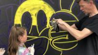 man teaching girl how to use spray paint can