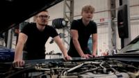 Two apprentices working on a Jaguar