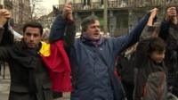 People holding hands in the Place de la Bourse, Brussels