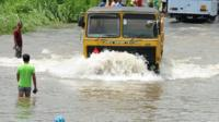 Sri Lankan commuters drive through floodwaters in Colombo