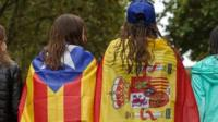 "Girls stroll through the centre of Figueras with the Spanish and a pro-independence ""Estelada"" Catalan flag on 30 September 2017"