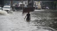 A man walks through a flooded street in Mumbai