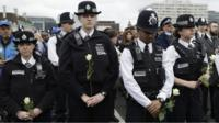 Police holding white roses on Westminster bridge